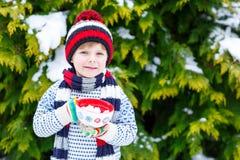 Śliczna chłopiec trzyma dużą filiżankę, gorącej czekolady marshmallo i napój i Obraz Stock
