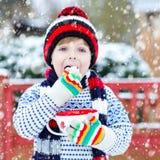 Śliczna chłopiec trzyma dużą filiżankę, gorącej czekolady marshmallo i napój i Fotografia Stock