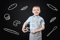 Śliczna chłopiec uśmiecha się marzyć o zostać kucharzem fotografia stock
