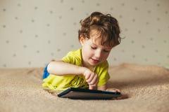 Śliczna chłopiec używa ochraniacza Dziecko bawić się z cyfrowym pastylki lying on the beach na łóżku cofee target2025_0_ target20 obrazy stock