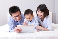 Śliczna chłopiec używa pastylka komputer osobisty z szczęśliwą rodziną Obrazy Royalty Free