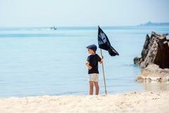 Śliczna chłopiec ubierał jak pirat na tropikalnej plaży Obrazy Stock