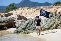 Śliczna chłopiec ubierał jak pirat na tropikalnej plaży Obraz Stock