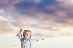 Śliczna chłopiec udaje być pilotowym mieniem jego ręki w górę zdjęcia stock