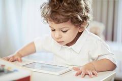 Śliczna chłopiec w białej koszulce, ogląda bajkę - lekki tło Uroczy mały naukowiec Obrazy Stock
