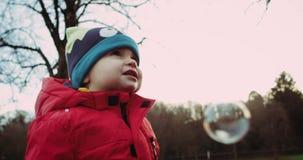 Śliczna chłopiec w czerwonej kurtce i śmiesznym kapeluszu ma zabawę z mydlanymi bąblami Patrzeje bąble i ono uśmiecha się Czerwon zbiory