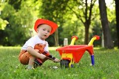 Śliczna chłopiec w czerwonym hełmie bawić się z wheelbarrow wewnątrz Zdjęcie Royalty Free