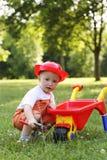 Śliczna chłopiec w czerwonym hełmie bawić się z wheelbarrow wewnątrz Obrazy Royalty Free