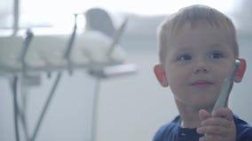 Śliczna chłopiec w dentystów biurowych bawić się trzyma medycznych narzędziach Beztroski dziecko odwiedza lekarkę leczenie dentys zbiory wideo