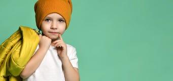 Śliczna chłopiec w koszulce, kapeluszu i kurtce w jego ręce pozuje przed zieloną błękit ścianą białych, zdjęcie royalty free