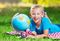 Śliczna chłopiec w parku z kulą ziemską Fotografia Royalty Free