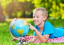 Śliczna chłopiec w parku z kulą ziemską Obraz Stock