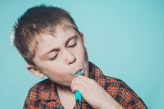 Śliczna chłopiec w piżamy szczotkuje zęby z pastą do zębów przed pora snu na błękitnym tle zdjęcie stock