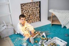 Śliczna chłopiec z bożonarodzeniowe światła siedzi na podłoga Obraz Royalty Free