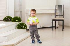 Śliczna chłopiec z filiżanką w pokoju Zdjęcia Royalty Free