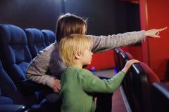 Śliczna chłopiec z jego macierzystym dopatrywanie kreskówki filmem w kinie fotografia stock