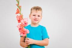Śliczna chłopiec z kwiatem w ręce na białym tle zdjęcia stock