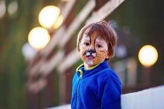 Śliczna chłopiec z malującą twarzą jako lew, mieć zabawę Zdjęcia Royalty Free
