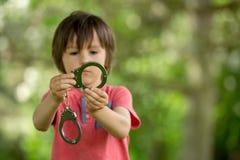 Śliczna chłopiec z ręka mankiecikami na jego rękach Zdjęcie Stock