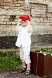 Śliczna chłopiec z walizką i czerwień kapeluszem Fotografia Stock