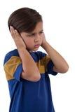 Śliczna chłopiec zakrywa jego ucho zdjęcia royalty free