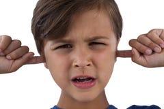 Śliczna chłopiec zakrywa jego ucho przeciw białemu tłu zdjęcia royalty free