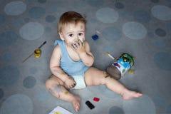 Śliczna chłopiec zakrywająca w farby obsiadaniu na podłoga wśród rzeczy dla twórczości zdjęcia stock