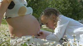Śliczna ciekawa mała dziewczynka słucha jej matki brzuch