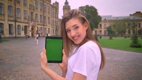 Śliczna cuacasian dziewczyna używa pastylkę, pokazywać zieleń ekran w kamerze, ono uśmiecha się, univercity w tle