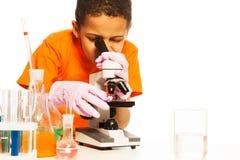 Śliczna czarna chłopiec patrzeje w mikroskop obrazy royalty free