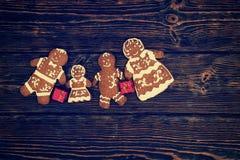 Śliczna domowej roboty piernikowa rodzina z małymi czerwonymi prezentami na zmroku wo Zdjęcia Stock