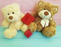 Śliczna dwa misiów rodziny zabawka z czerwonym pudełkiem na błękitny drewnianym i menchiach Obrazy Royalty Free