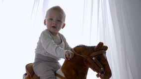Śliczna dziecięca chłopiec cieszy się chlanie na zabawkarskim koniu w domu zbiory