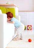 Śliczna dziecięca imbirowa chłopiec próbuje wspinać się leżankę w domu Obraz Stock