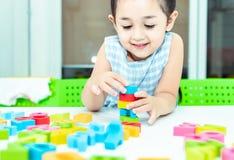 Śliczna dzieciak kobieta bawić się z zabawkarskim projektantem na podłodze w domu Dziecko dziewczyna ekscytuje podczas gdy ba zdjęcia stock