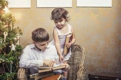 Śliczna dziecko chłopiec, dziewczyna w krześle czyta książkę w wnętrzu i obrazy stock