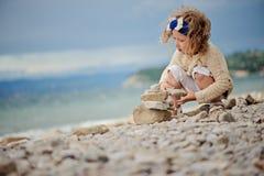 Śliczna dziecko dziewczyna bawić się skały wierza na lato plaży i buduje Zdjęcie Royalty Free