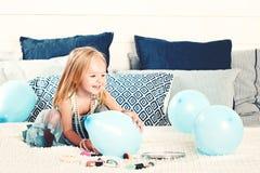 Śliczna dziecko dziewczyna Ma zabawę z błękitem Szybko się zwiększać w domu Fotografia Stock
