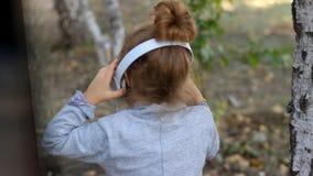 Śliczna dziecko dziewczyna słucha muzyka i śpiew w hełmofonach piosenka w parku z brzozami zbiory