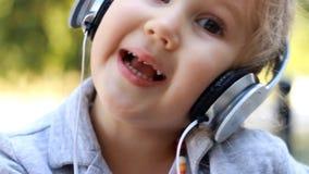 Śliczna dziecko dziewczyna słucha muzyka i śpiew w hełmofonach piosenka Portreta zbliżenie zdjęcie wideo