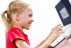 Śliczna dziewczyna bawić się na laptopie Zdjęcia Stock