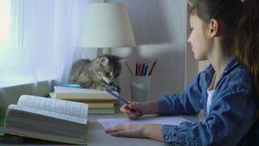 Śliczna dziewczyna bawić się z jej zwierzę domowe kotem zamiast robić pracie domowej zbiory
