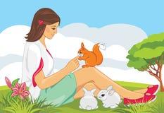 Śliczna dziewczyna bawić się z wiewiórką i królikami Fotografia Royalty Free