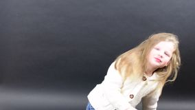 Śliczna dziewczyna czesze jej włosy Mała dziewczyna ubiera w zimy odzieży Śliczna mała dziewczynka na czarnym tle zdjęcie wideo