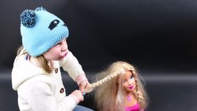 Śliczna dziewczyna czesze tytułowanie głowę Mała dziewczyna ubiera w zimy odzieży Śliczna mała dziewczynka na czarnym tle zdjęcie wideo
