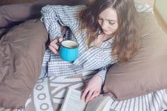 Śliczna dziewczyna czyta książkę podczas gdy kłamający w łóżku Zdjęcie Stock