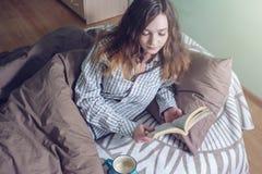 Śliczna dziewczyna czyta książkę podczas gdy kłamający w łóżku Obraz Royalty Free