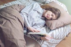 Śliczna dziewczyna czyta książkę podczas gdy kłamający w łóżku Obraz Stock