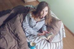 Śliczna dziewczyna czyta książkę podczas gdy kłamający w łóżku Zdjęcie Royalty Free
