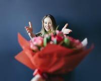 Śliczna dziewczyna dostaje bukiet czerwoni tulipany Chłopak daje tulipany Zdjęcia Stock